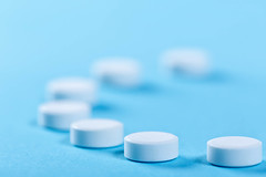 White round pills on blue background