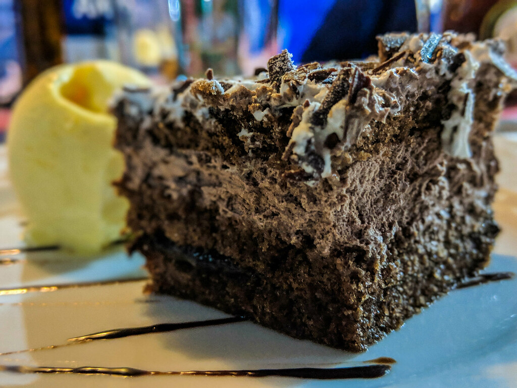 A chocolate cake with ice cream in the background