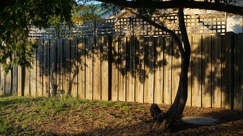Fence with shadows in the evening with a manhole