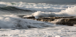 Rocky seashore with wavy ocean and waves crashing on the rocks | by mpalis