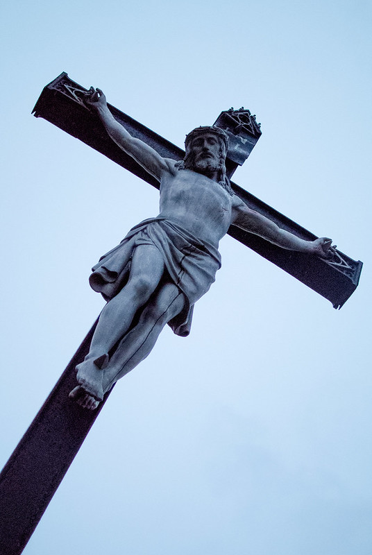 Jesus Christ on a cross against an overcast evening sky