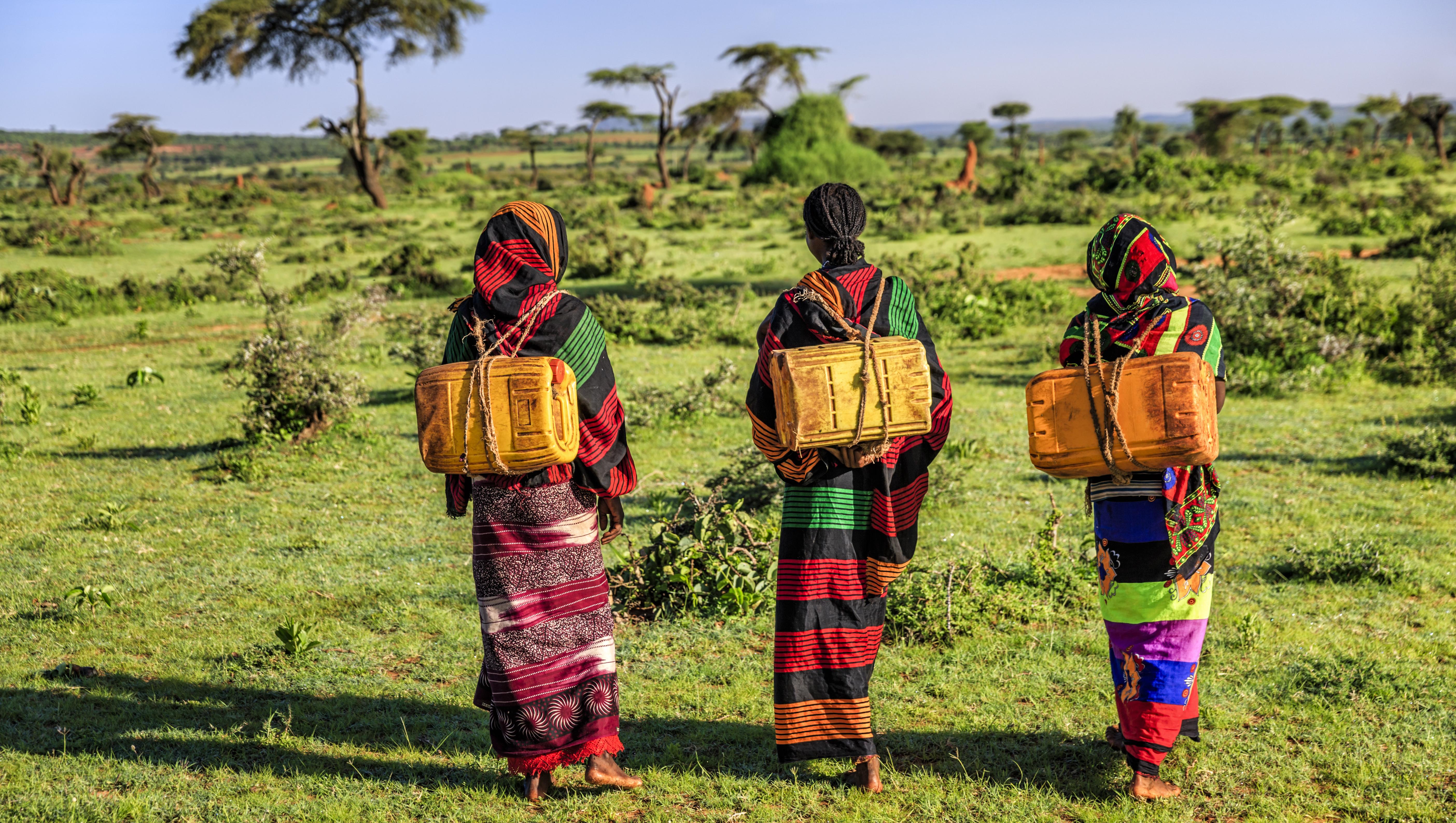 Three young women in rural Kenya carrying water whole walking.