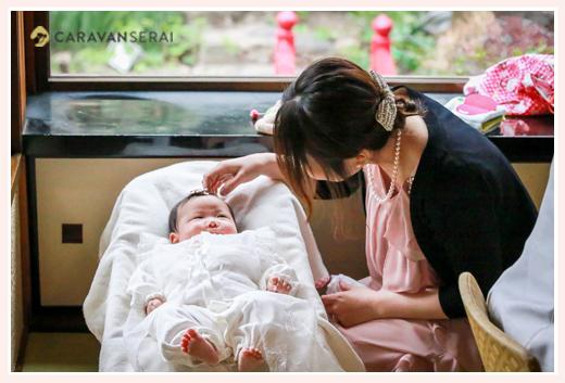 ベビードレスを着た赤ちゃんをあやすママ