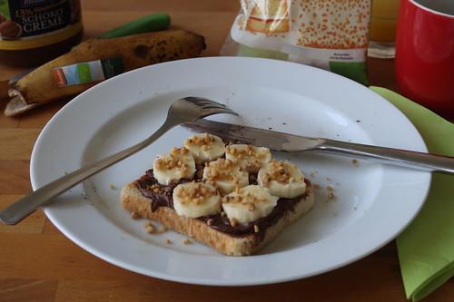 Toast mit Schokoladencreme, Bananenscheiben und Haselnusskrokant