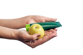 Woman hands holding green apple and beauty hand cream. Isolated on white | by wuestenigel