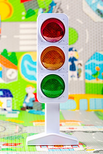 Toy model of traffic light with the image of the road in the background | by wuestenigel