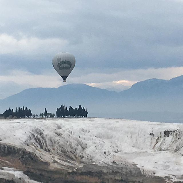Hot air balloon over travertines at Pamukkale