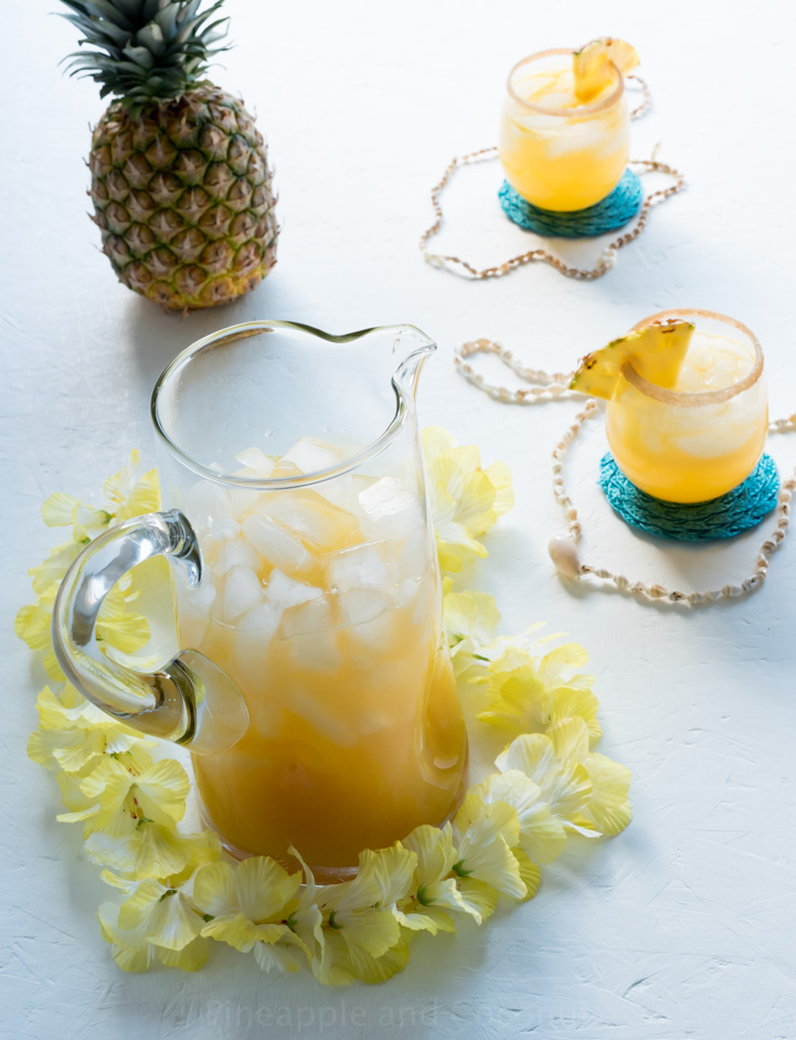 large glass pitcher of rum punch, whole pineapple, two small glasses of rum punch, yellow flower lei