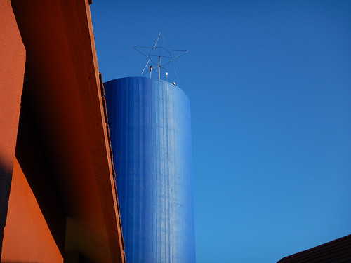 An orange wall with a blue water tower in Huatalco, Mexico