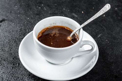 A Cup of hot coffee with a coffee spoon on a dark background | by wuestenigel