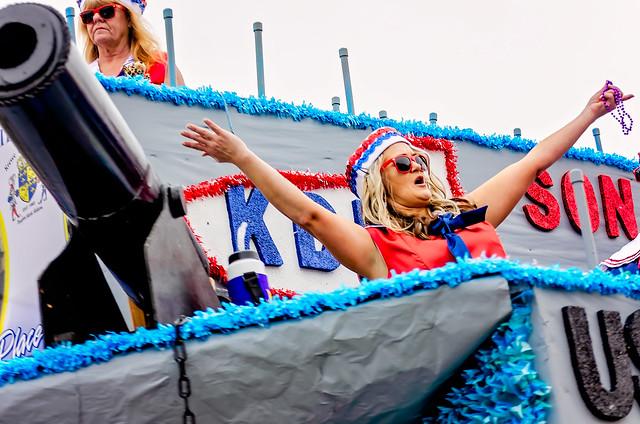 Woman throws Mardi Gras beads at Krewe de la Dauphin Mardi Gras parade in Dauphin Island, Alabama