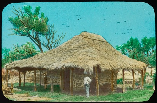 Man standing outside stone building with a thatched roof, Central Queensland, ca. 1910