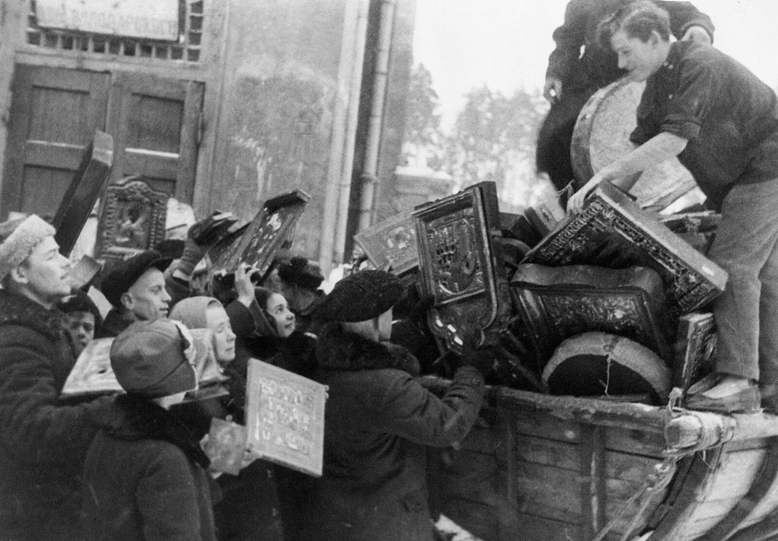 24 февраля 1930. «Москва. Эти мужчины и женщины страны Советов с улыбкой укладывают религиозные символы, собранные в рабочих общежитиях на грузовик, который повезет их к месту аутодафе. Пять тысяч икон были сожжены во время одного массового праздника, в к