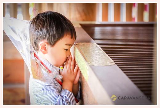神社でご参拝する男の子
