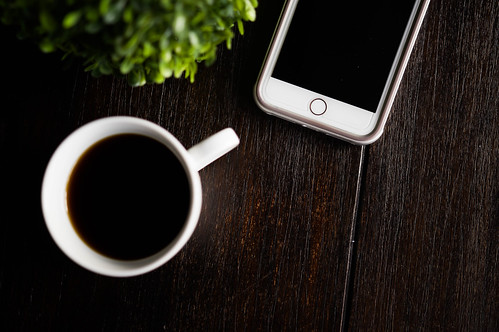 Coffee cup and phone on a wooden table   by wuestenigel