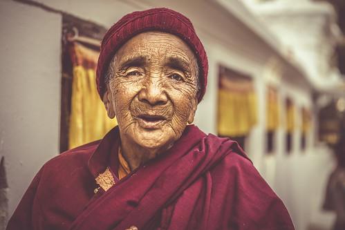 tibetan buddhist nun street portrait portraiture outdoors boudhanath great stupa woman old happy peaceful purposeful clear content sony a6000 alpha ilce6000 6000 ilcenex sigma 60mm f28 emount dn art hat robes maroon red elegant beautiful prayer wheel buddha tibet jharung khashor