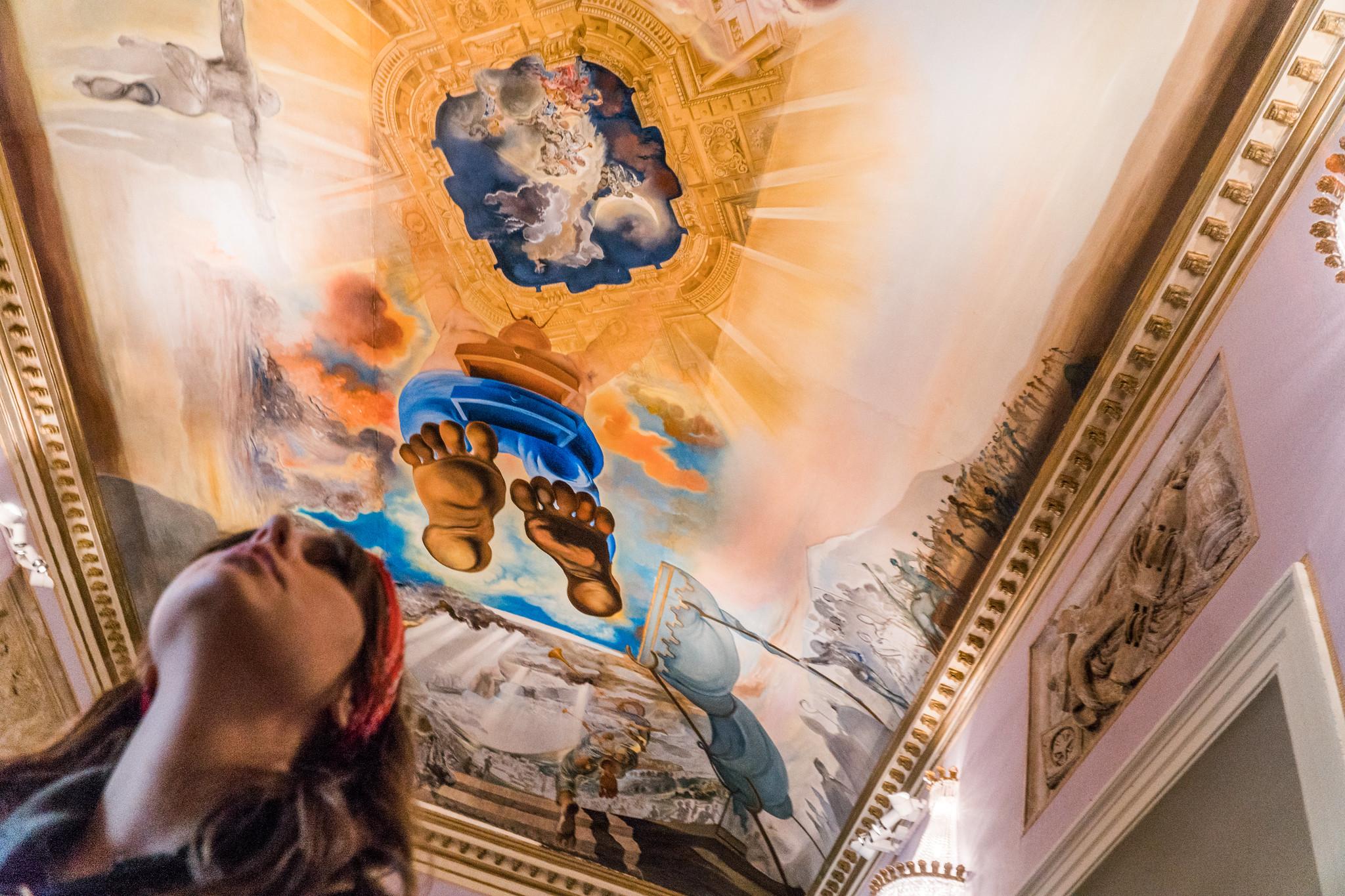 un soffitto con un dipinto di piedi immensi e una ragazza sotto