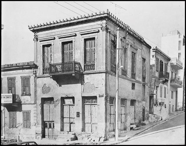 """Βασιλέως Γεωργίου 27 και Θεάτρου, Πειραιάς (κατεδαφισμένο). Φωτογραφία του Στέλιου Σκοπελίτη από το βιβλίο """"Νεοκλασσικά σπίτια της Αθήνας και του Πειραιά"""" Εκδόσεις """"Δωδώνη"""", Αθήνα, 1975."""
