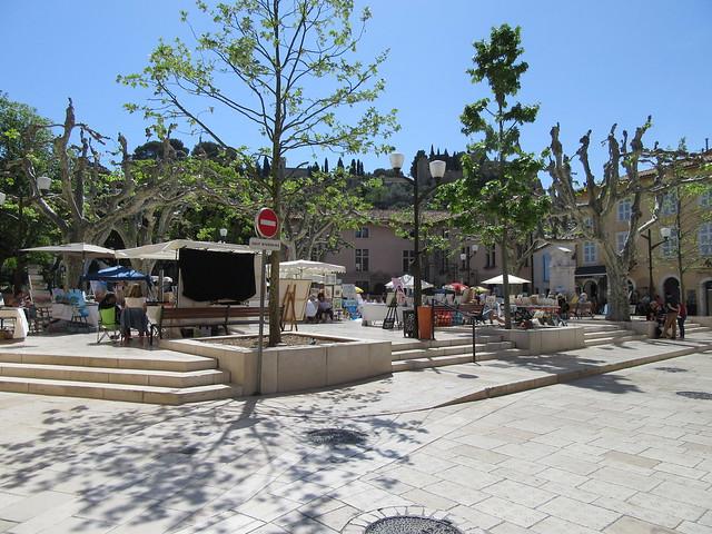 Ein Platz mit hellen Steinen und enigen Steinen. Auf dem Platz stehen ein paar Marktstände. Einige Bäume spenden Schatten.