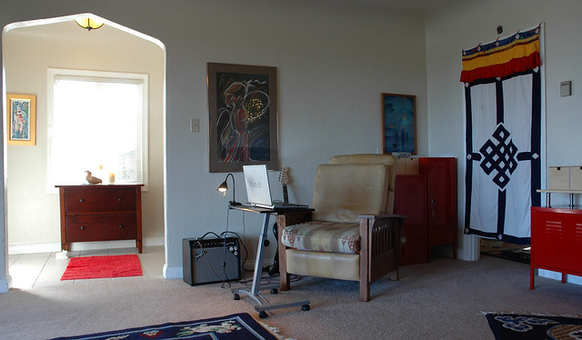 Entrance, laptop, home office, rolling table, reclining chair, southwest design seat, guitar, Fender speaker, paintings, female figure, red metal storage cases, Tibetan door cover, lamp, San Mateo, CA, USA