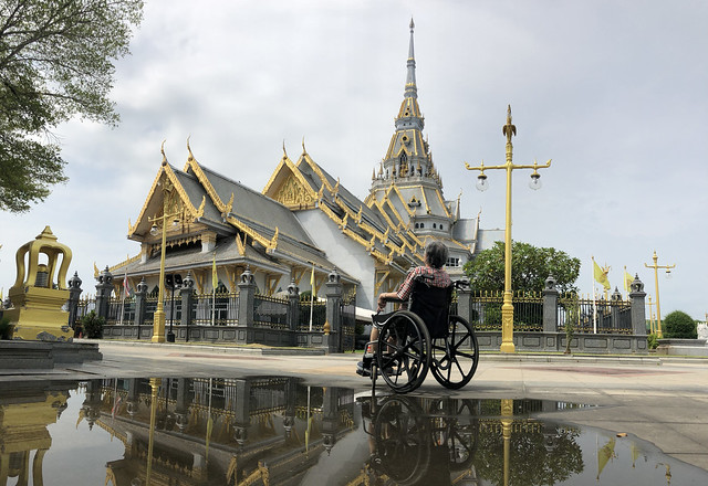 A senior woman sitting on the wheelchair seeing the grand hall of Wat Sothorn Wararam Worawihan temple (Chachoengsao Province)