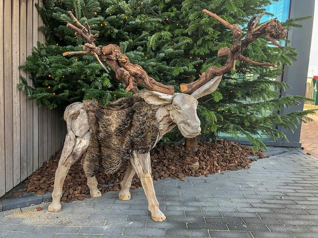 Holzfigur von einem Rentier mit Fellmantel vor einem Tannenbaum
