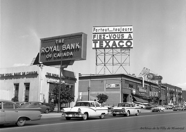 Vue vers le sud-est du boulevard Décarie, depuis l'intersection de l'avenue Van Horne. L'immeuble situé au 5995 (alors occupé par la Banque royale) existe toujours. 6 juin 1961. VM105-Y-3_556-011. Archives de la Ville de Montréal.