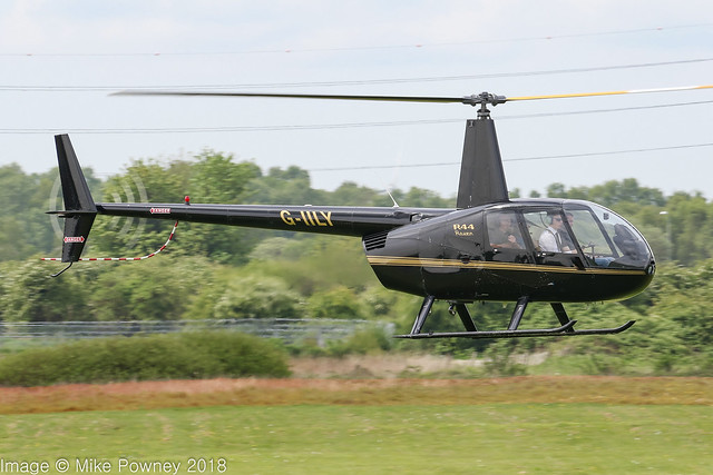 G-IILY - 2000 build Robinson R44 Raven, waiting to cross the active on departure from Barton
