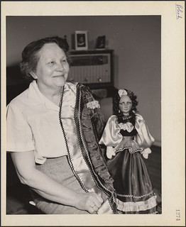 Mrs. Anna Czerwinski displaying a doll that she has dressed in the national costume of her Polish homeland / Mme Anna Czerwinski montrant une poupée qu'elle a habillée du costume national de son pays natal, la Pologne