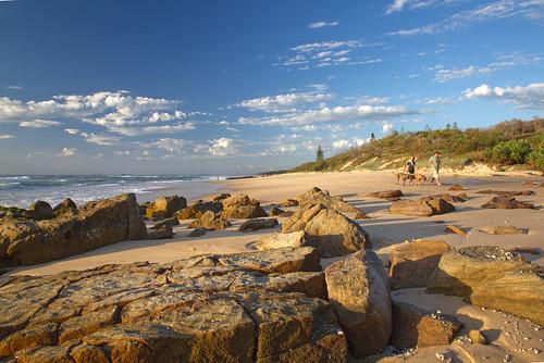australia queensland sunshinecoast pointarkwright landscape view rocks sand beach shadows sky clouds trees green waves sea ocean water dogs people fisherman