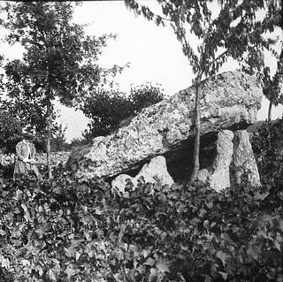 Woman standing beside large stone/dolmen