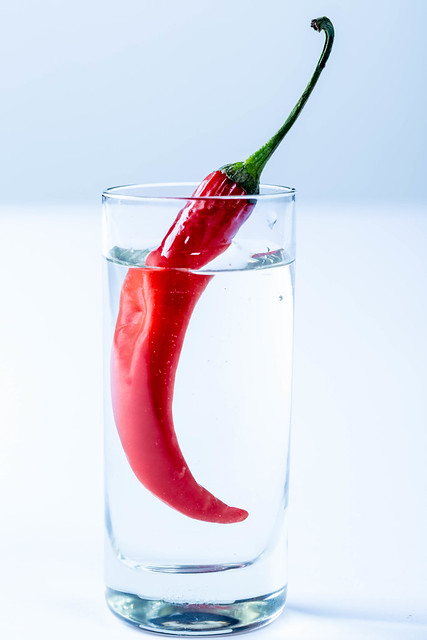 Shot of vodka and red hot chili pepper on white background