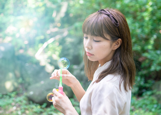 Young woman looking at soap bubbles in forest