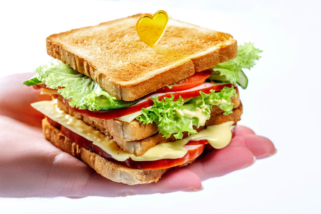 Appetizing sandwich with lettuce, tomatoes, cheese and ham on the man's hand