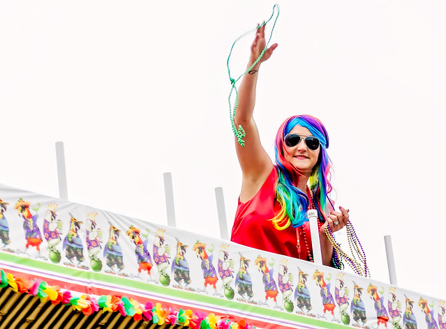 Woman throwing Mardi Gras beads at Krewe de la Dauphin Mardi Gras parade in Dauphin Island, Alabama