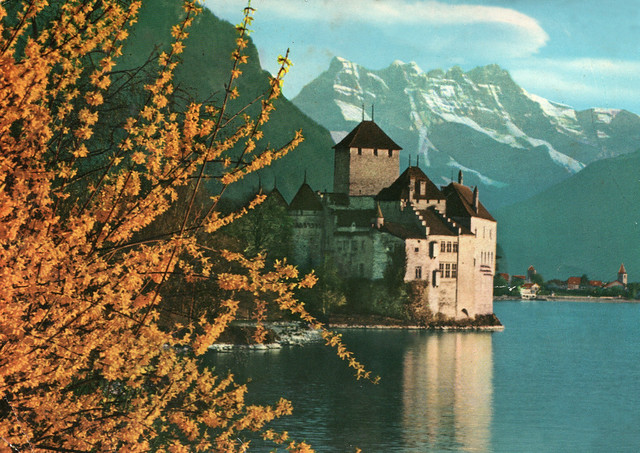 ,Switzerland - Castle of Chillon and the Dents du Midi Mt. composed of seven distinct summits and reach a height of 3257 m