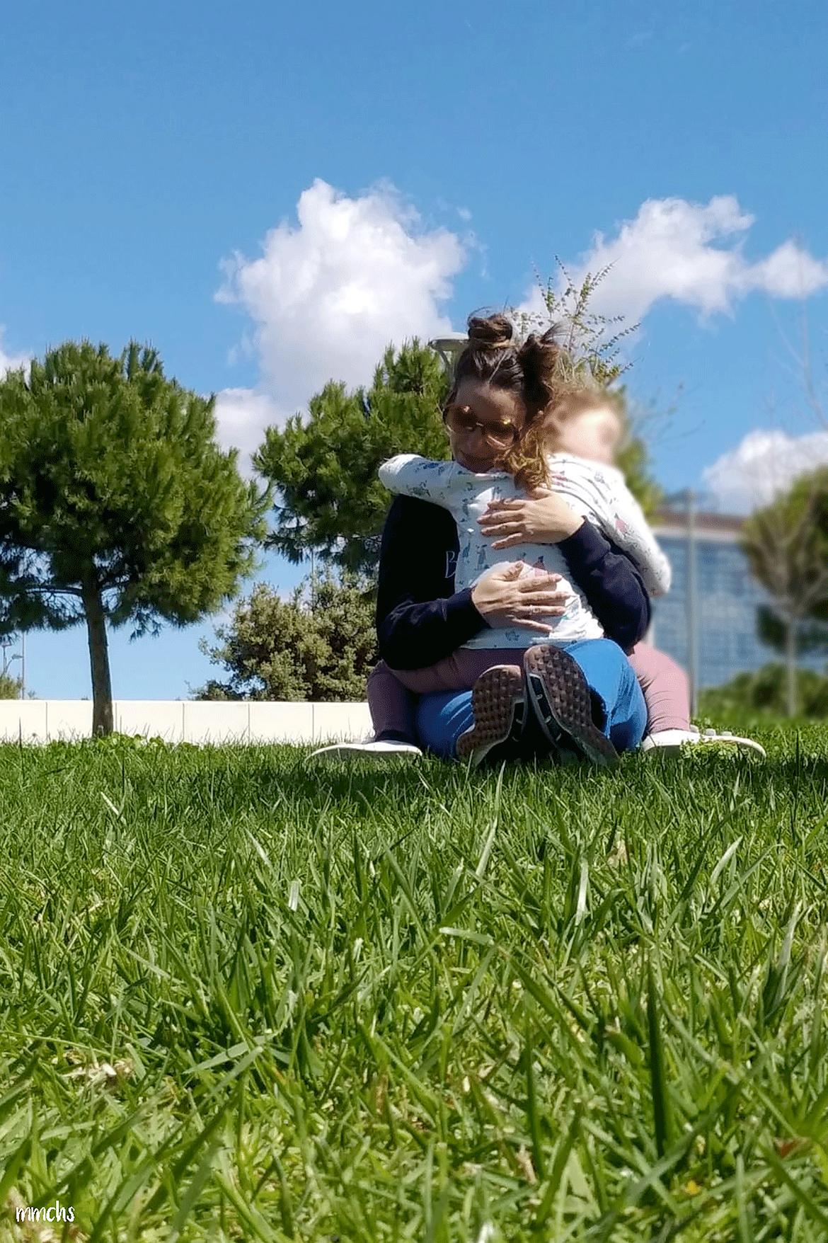 madre e hija abrazadas en el césped