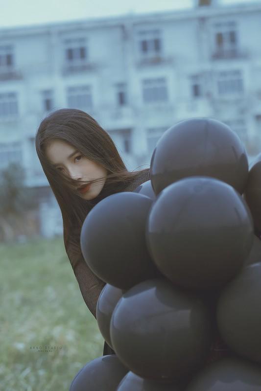 stock chân dung cô gái áo đen cầm chùm bóng bay đen