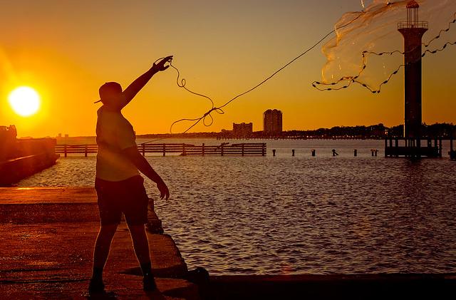 Man casting brill net at Broadwater Beach Marina in Biloxi Mississippi