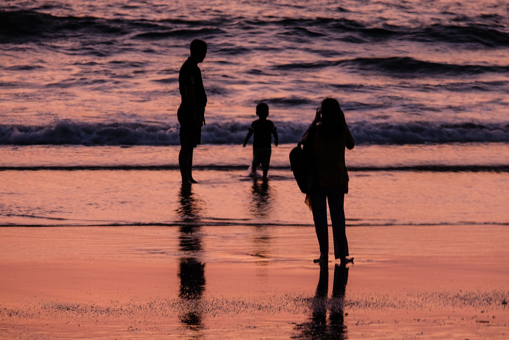 Silhouettes of Parents Taking Photos of Their Son on the Beach at Sunset