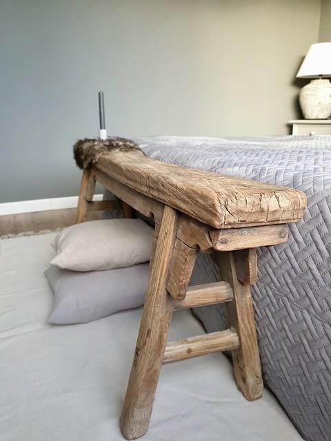 Sober houten bankje achter het bed