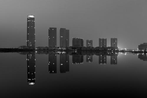 yixing wuxi jiangsu china prc sunrise dawn softlight water reflections calm mirror dongjiu lake highrise skyscrapers buildings city architecture tall blackandwhite bw mono monochrome