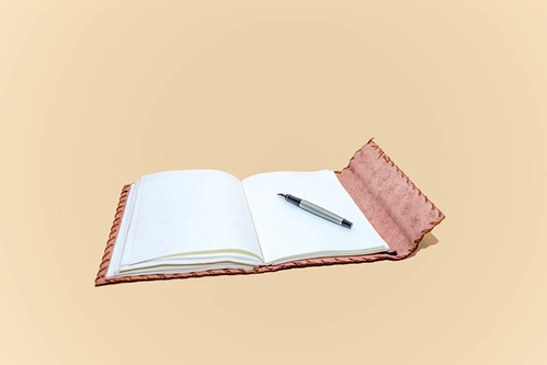 Leather notepad with blank pages and pen on cream background | by wuestenigel