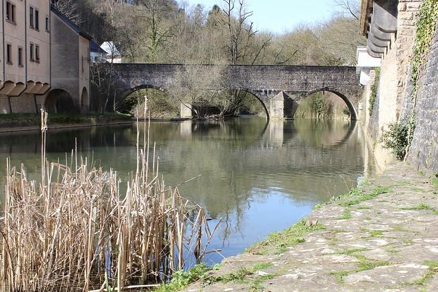 Eine Brücke mit drei Bögen überspannt einen Fluss, der an beiden Ufern von Häusern begrenzt ist. Im Vordergrund ist Schilf.