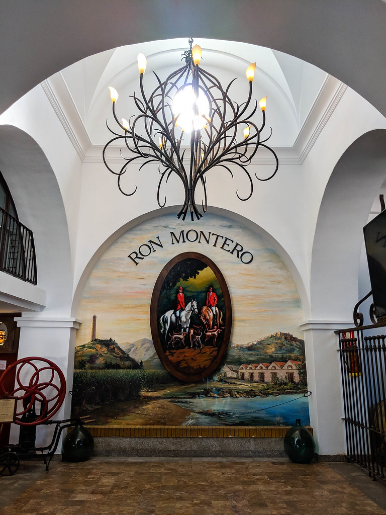 The entrance to the bodega, with a chandelier and a painting of the logo of the rum distilery on the wall