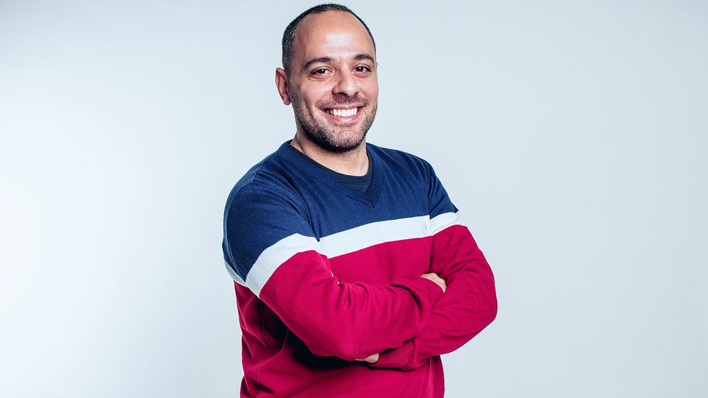 A studio portrait of DBA student Amine Moussa stood smiling at the camera with his arms crossed.