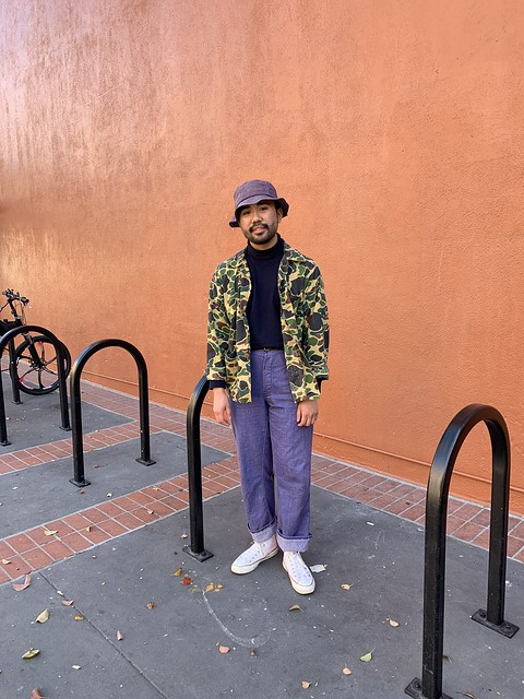 Ethan - bucket hat, camo chore coat, cotton turtleneck, cotton work trousers, white socks, converse