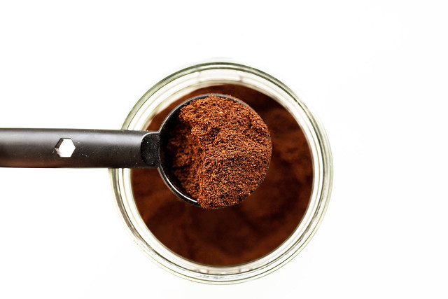 Top view of spoon of ground coffee and a jar of coffee on white background