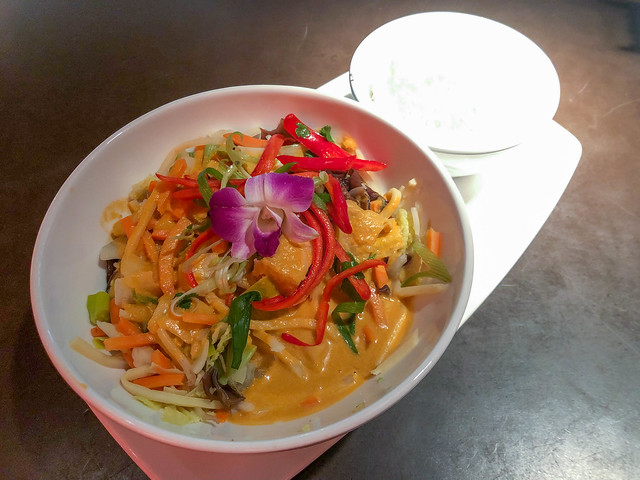 Vegan thai curry decorated with purple orchid flower in white bowl