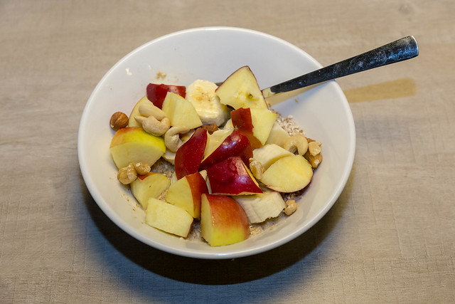 Organic vanilla chia porridge with apples, bananas and various nuts in white bowl